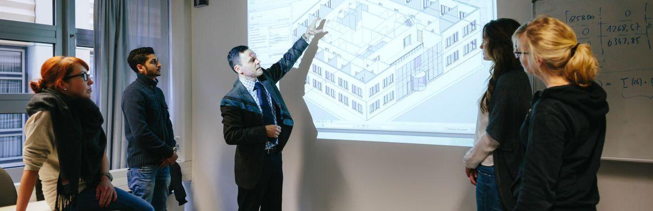 Professor erklärt Studierenden eine Gebäudesimulation